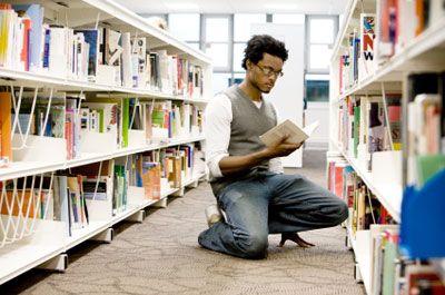 image of student reading a book in the Library
